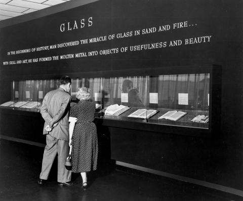Black and white photo of two people standing looking through a narrow glass case at books on display in a museum. The image is from the 1950s.
