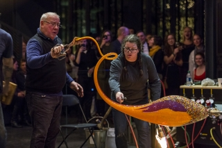 Two gaffers create a swirling tail on an orange and purple oval of molten glass