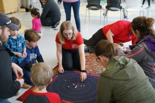 A group of visitors and volunteers sit next to a mat with marbles on it.