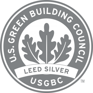 "Round silver logo with 3 leaves with the text ""U.S. Green Building Council USGBC LEED Silver"""
