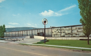 1951 photograph of the Corning Museum of Glass. A glass, rectangular building with a lawn, trees, and a glory-hole-inspired logo on a pole are in front of the building.