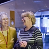 Two adults with museum name tags smile at each other while in an open gallery