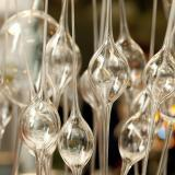 A row of vertical clear glass spheres with long, clear glass rods at the top and bottom of each sphere