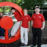 Six teens smile at the camera while in front of the CMoG logo sculpture, which is a red circle with a red dot in the middle.