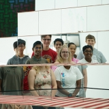 Seven teens stand in a group and smile at a mirror, which distorts their heads from their bodies.
