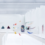 An expansive gallery space with white curved walls and large scale sculptures made of colored glass on pedestals and hanging from the ceiling.